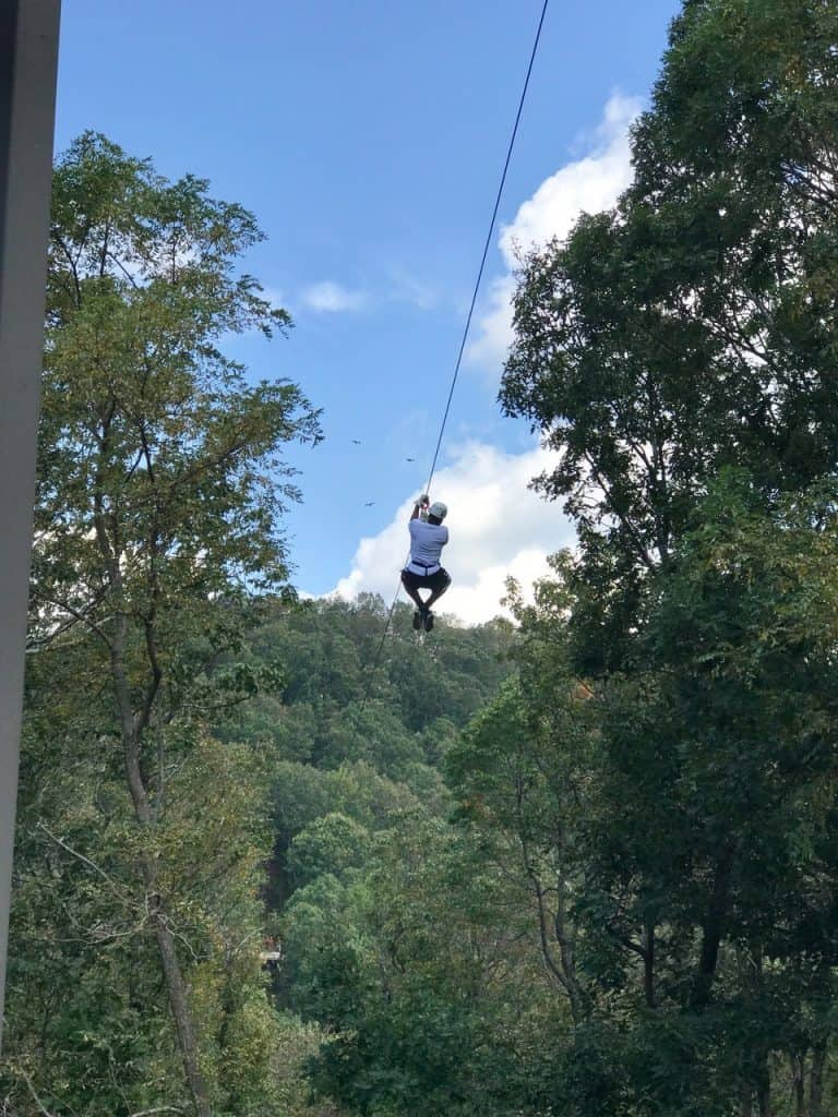Person on going down a zipline surrounded by green trees and an open blue sky above.